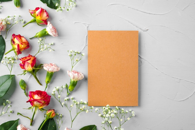 Blank notepad page with flower branch, top view