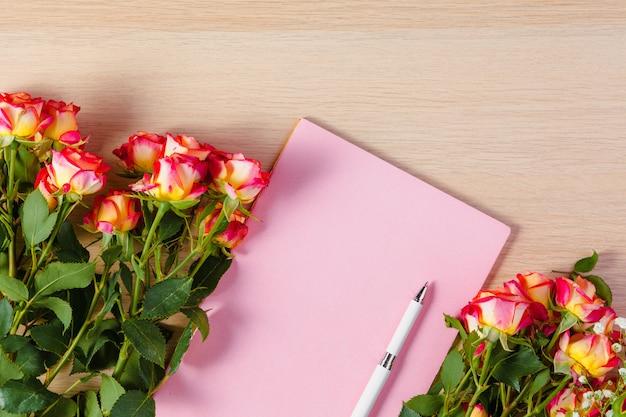 花の枝を持つ空白のメモ帳ページ
