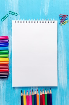 Blank notepad page with pencils, markers, paper clips. back to school concept.