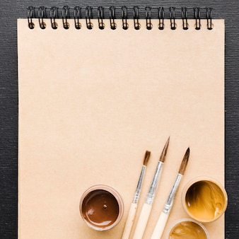 Blank notepad and paint brushes