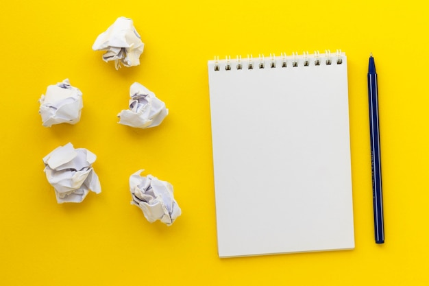 Blank notepad, pen and crumpled paper balls on yellow. writing message. new or bad idea. flat lay.
