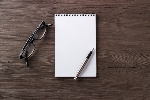 Blank notepad pen and glasses