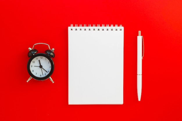 Blank notepad, pen and mini alarm clock on red background. time management. notebook for ideas, message, list and inspiration.