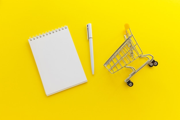 Blank notepad and pen and mini supermarket cart on yellow background. online shopping, list concept. flat lay, top view, copy space.