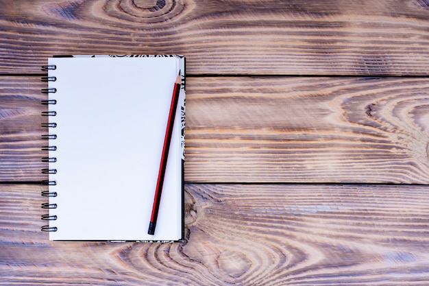 Blank notepad and pencil on wooden background.
