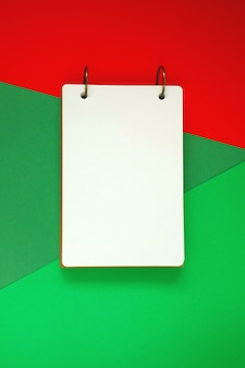 Blank notepad on red green bright background.notebook on trend graphic background.flat lay, top view, copy space