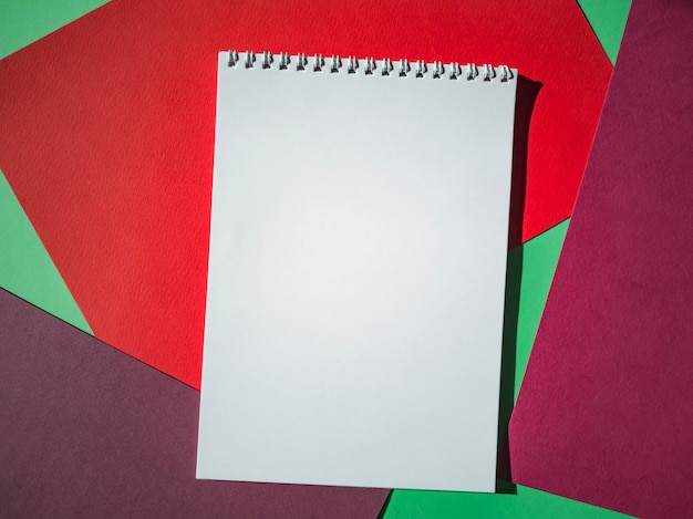 Blank notepad on a spiral with white pages on colored sheets of paper. top view, minimalism, flat lay.