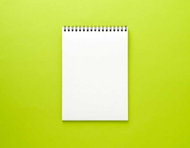 Blank notepad white page on green desk, color background. top view,  empty  for text.