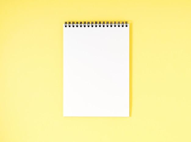 黄色の机、色の背景上の空白のメモ帳白いページ。テキストの空のトップビュー。