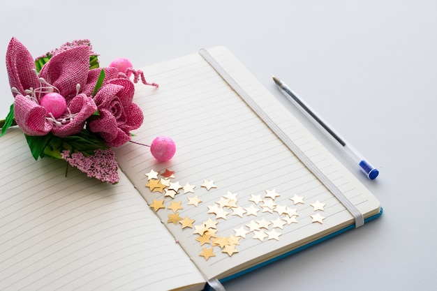 Blank notepad with bouquet of spring flowers and glimmer stars.