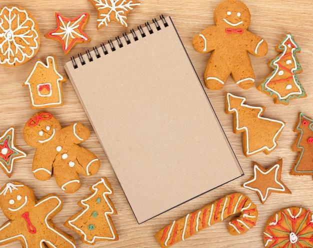 나무 테이블에 크리스마스 진저 쿠키가 있는 빈 메모장