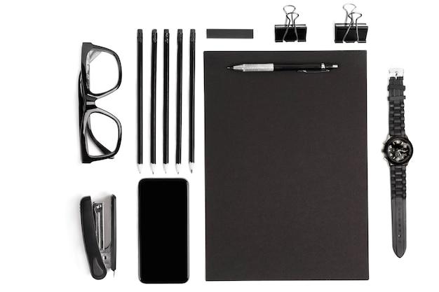 クリップ、ペン、メガネフラットで空白のメモ帳を置きます。白い背景に黒い事務用品と眼鏡のセットのトップビュー