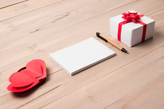 Blank notepad with gift box on table