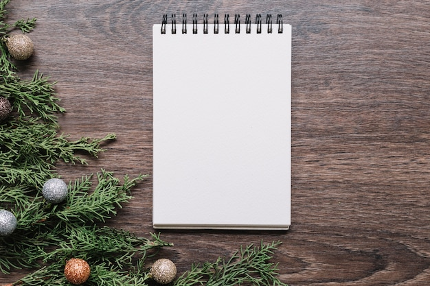Blank notepad with green branches on table