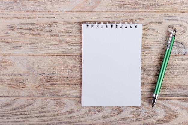 木製のオフィスのテーブルの上にペンで空白のメモ帳