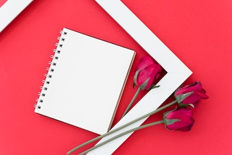 Blank notepad with red roses in frame