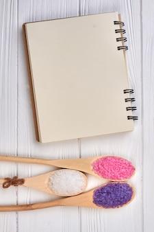 흰색 나무 책상에 소금을 넣은 숟가락이 있는 빈 메모장.