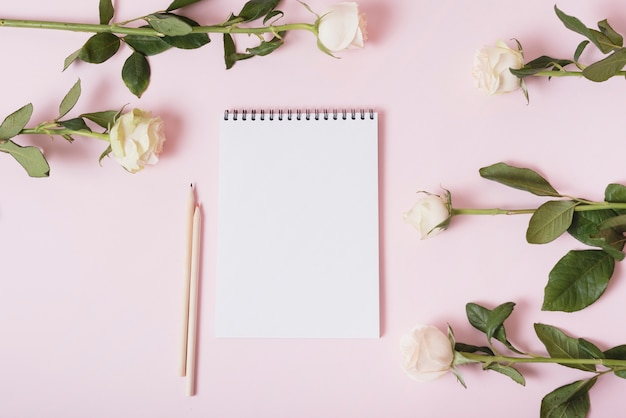 Blank notepad with two colored pencils surrounded with roses on pink backdrop