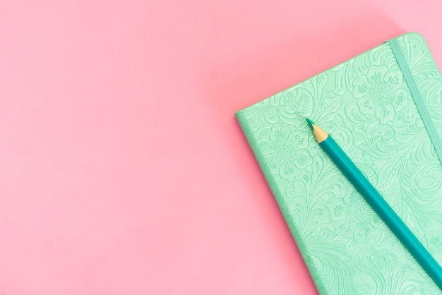 Blank notepad with yellow pencil on pink and blue background