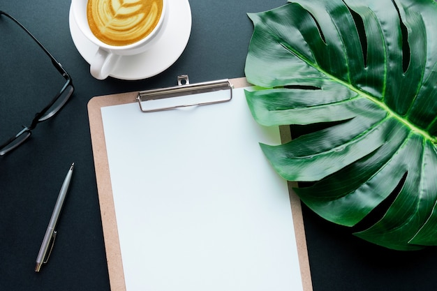 Blank notepaper with tropical leaves and accessories laying on black table.home office,workspace design backgrounds,flat lay,top view