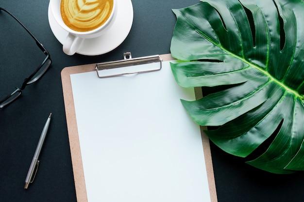 Пустая бумага для записей с тропическими листьями и аксессуарами, лежащими на черном столе. домашний офис, дизайн рабочего пространства, плоская планировка, вид сверху