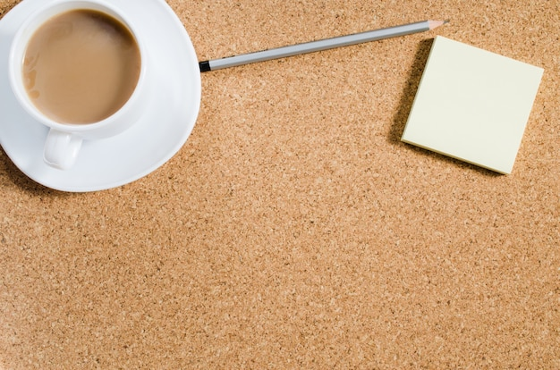 Blank notes and cup of coffee on cork board