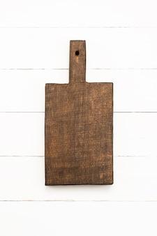 白い木製の背景に空白のオークまな板