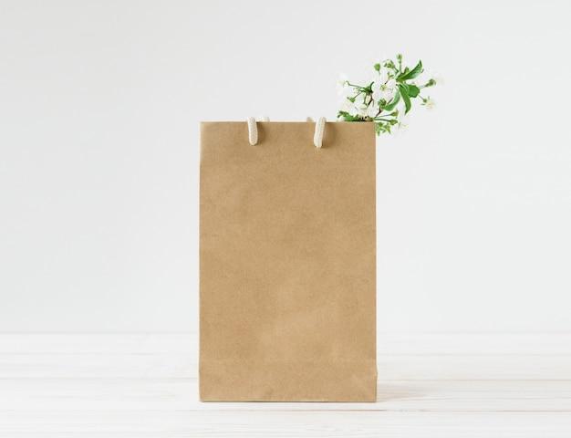 ハンドル付きの茶色のクラフト ペーパー バッグの空白。白い背景。新鮮な花。