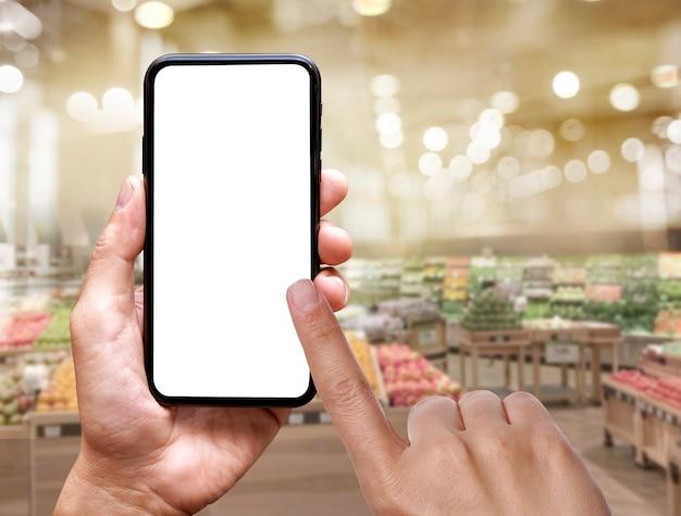 新鮮な市場で手にモバイル画面の空白