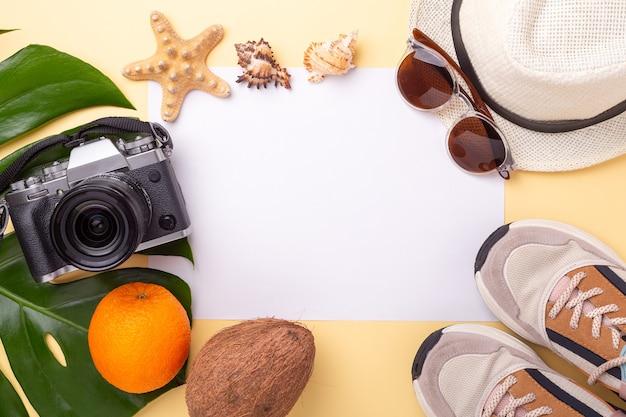 파스텔 노란색 배경에 종이, 몬스 테라 잎, 카메라, 운동화, 여름 액세서리의 빈