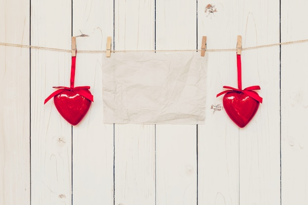 Blank old paper and red heart hanging on wood board background with space.
