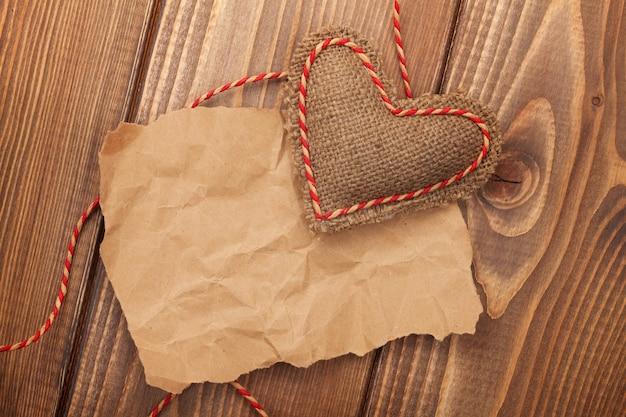空白の古い紙片と木製の背景の上のヴィンテージ手作りバレンタインデーおもちゃの心