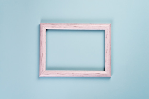 Blank old wooden frame for photos or different pictures on a pastel blue background.