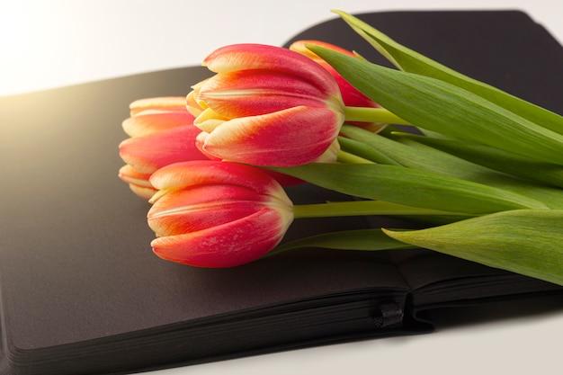 テキストまたはレタリングのためのスペースと春の赤いチューリップで飾られた空白の開いている黒い日記(ノート、スケッチブック)。回顧録、回想、人生の物語を書くことの概念。記念日の構成。