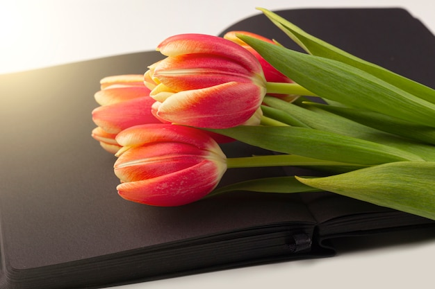 Blank open black diary (notebook, sketchbook) decorated with spring red tulips with space for text or lettering. concept of writing memoirs, reminiscence, life story. composition for memorial day. Premium Photo