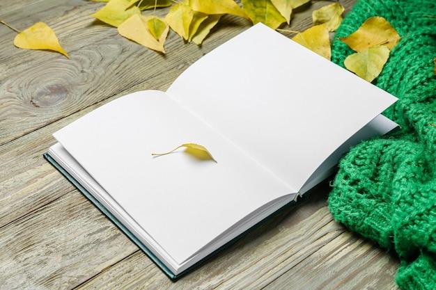 Пустая открытая книга и осенние листья на деревянных
