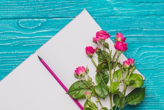 Blank open book with pencil and decorative flowers