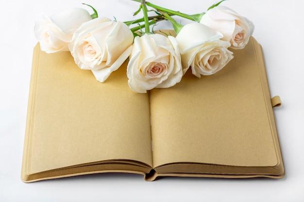テキストまたはレタリングのためのスペースを持つ白いバラで飾られた空白の開いている日記(ノート、スケッチブック)。