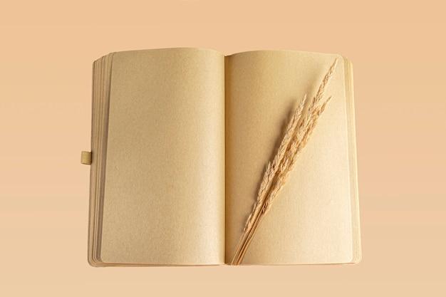 秋の草で空白の開いた日記(ノート、スケッチブック)。手紙、願い、目標、計画、ライフストーリーを書くことの概念。秋の構成植物標本。テキスト用のスペースをコピーする