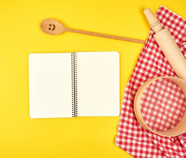 Пустой открытый блокнот и деревянные кухонные принадлежности