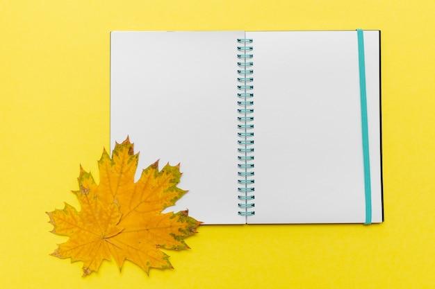 空白の開いたノートブックと黄色のカエデの葉が黄色の背景にあります。秋のシンボル。こんにちは10月のコンセプト。学校のコンセプトに戻ります。ビジネスコンセプト
