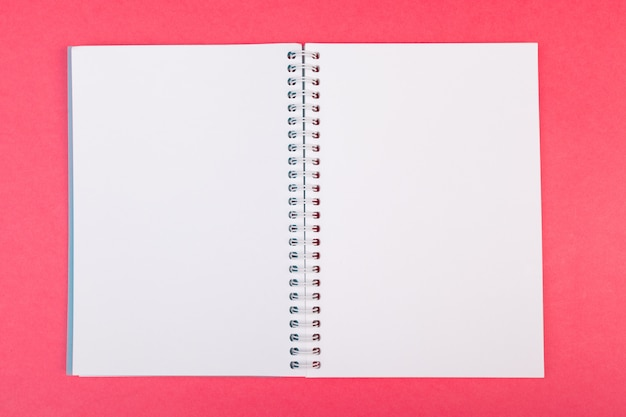 Blank open notebook on bright pink  top view