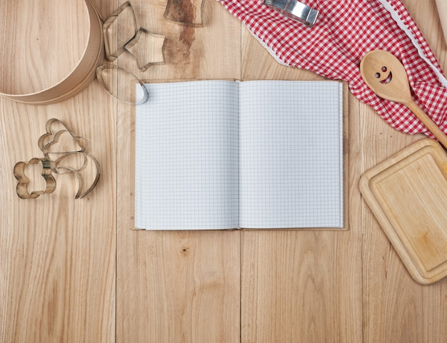 Blank open notebook in line and wooden kitchen accessories
