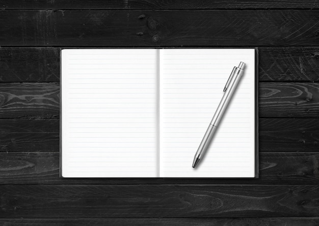 Blank open notebook and pen mockup isolated on black wood