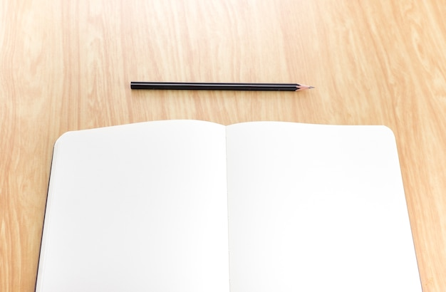 Blank open notebook with black pencil on wood table,business template