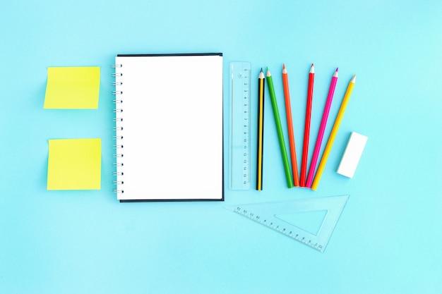 空白のシートとひな形と色鉛筆定規の周りの空白の開いているノートブック