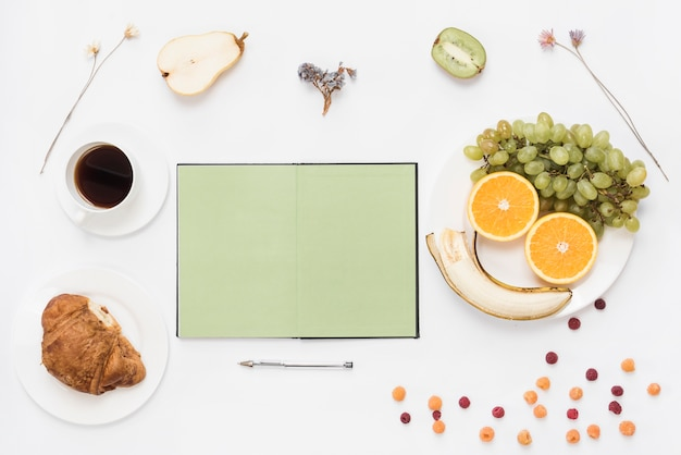 Blank open notebook with pen; croissant; coffee and fruits on white background