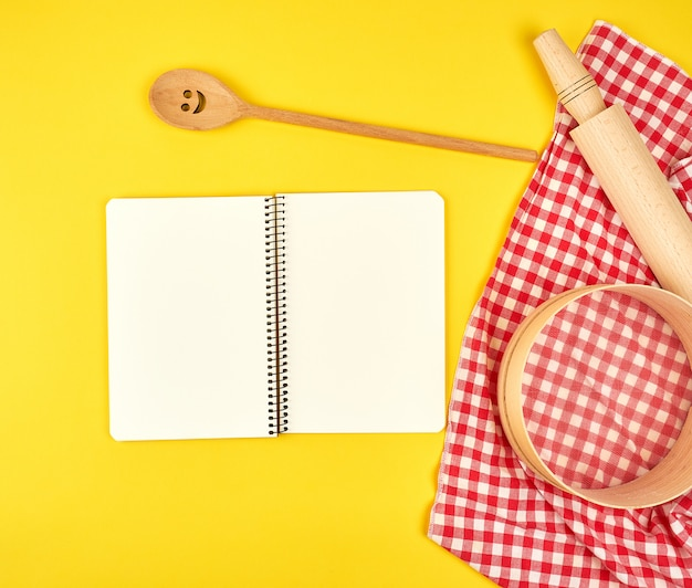 Blank open notebook and wooden kitchen accessories