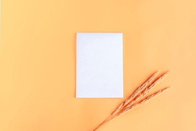 秋の草で空白の開いたページ(ノートブック、スケッチブック)。手紙、願い、目標、計画、ライフストーリーを書くことの概念。秋のモックアップ。テキスト用のスペースをコピーする