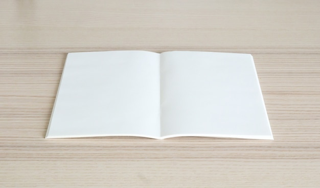 Blank open paper book on wood table background
